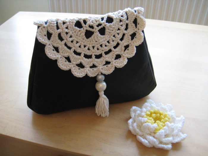 Doily flap on leather clutch bag
