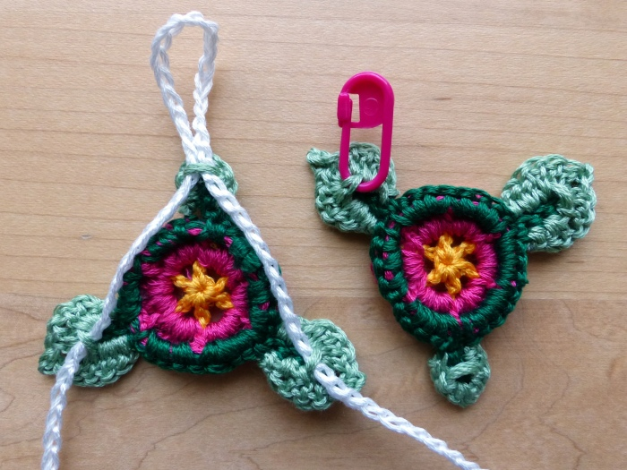 Use the tails to sew loops on the backs of the leaves (as indicated by the stitch marker).  Thread the ties as shown.